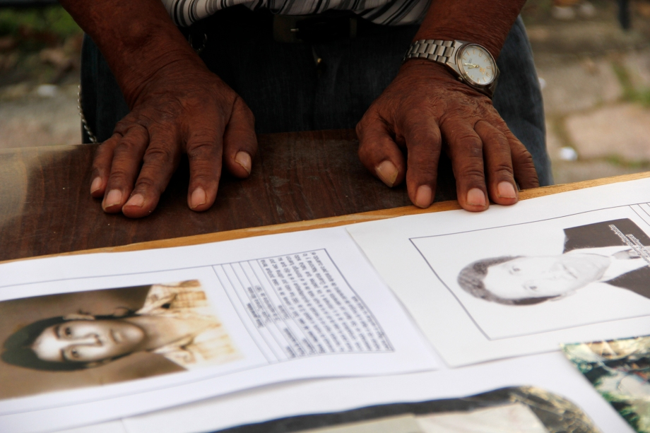 A man pauses from constructing a poster of family victims of the armed conflict in El Salvador from 1980-1992.