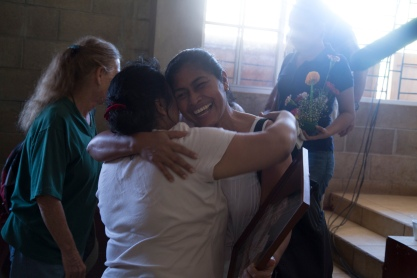 Photo of a joyous women hugging another woman holding the picture of a friend.