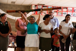 Photo of a woman holding a rainstick high amongst a group of Santa Marta residents.