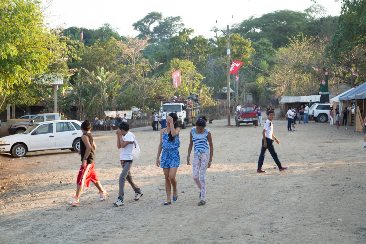 A group of teenagers cross the Santa Marta town plaza at dusk.