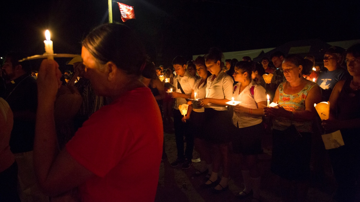 A woman and a group of students attend a candlelight vigil in Santa Marta, El Salvador.