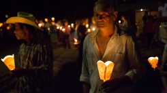 A Santa Marta resident holds a candle at a candlelight vigil.